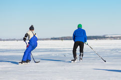 Mature man rushing to the pack while playing hockey on a frozen river Dnepr. Dnepr, Ukraine - January 22, 2017: Mature man rushing to the pack while playing stock image