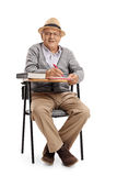 Mature man in a school chair taking notes Stock Photography