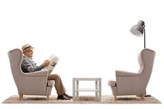 Mature man seated in an armchair reading a newspaper Stock Photo