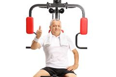 Mature man seated on an exercise machine holding his thumb up Stock Photo