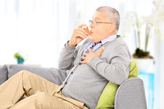 Mature man seated on a sofa taking asthma treatment at home Stock Photos