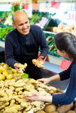 Mature man selling ginger to female customer Royalty Free Stock Photo