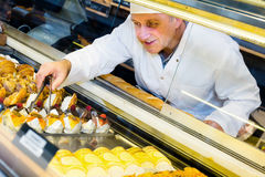 Mature man selling  tasty confectionery products Stock Images