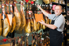 Mature man selling tasty Spanish jamon in store Royalty Free Stock Images