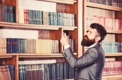 Mature man with serious face. Professor stands in big library and choose book. Bearded man in expensive suit in his stock images