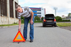 Mature man sets triangle warning sign Royalty Free Stock Image