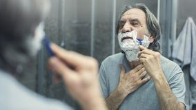Mature man shaving in front of mirror stock images