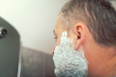 Mature man shaving in front of mirror Stock Photography