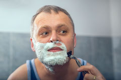 Mature man shaving in front of mirror Royalty Free Stock Photography