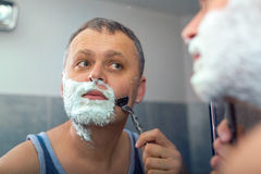 Mature man shaving in front of mirror Royalty Free Stock Photos