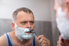 Mature man shaving in front of mirror Royalty Free Stock Images