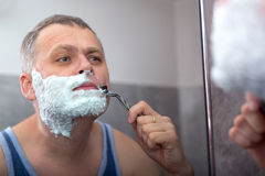 Mature man shaving in front of mirror Stock Photo