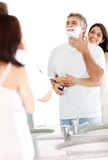 Mature man shaving his wife holding her husband Royalty Free Stock Photo