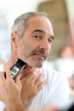Mature man shaving with razor Royalty Free Stock Photography