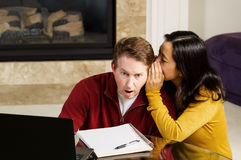 Mature Man shocked from word of woman coworker while working fro. Photo of mature couple, with women whispering into ear of men who is shocked, while working royalty free stock images