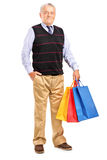 Mature man with shopping bags. Full length portrait of a mature man with shopping bags on white background royalty free stock images