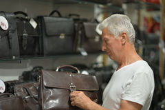 Mature man on shopping. Choosing leather bag Royalty Free Stock Images