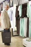 Mature man shopping in clothes shop, carrying shopping bags, smiling, side view, portrait Stock Photo