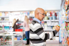 Mature man shopping in the supermarket. With people in the background royalty free stock photography