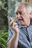 Mature man shouting into the phone. Vertical image of a mature man shouting into the phone Stock Image