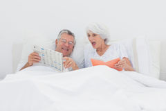 Mature man showing his newspaper to his wife Royalty Free Stock Photos