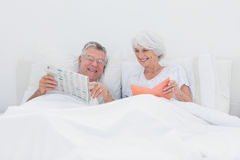 Mature man showing newspaper to his wife Royalty Free Stock Photography