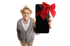 Mature man showing a phone wrapped with a red ribbon as a gift Stock Photos