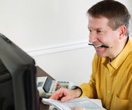 Mature man showing stress while doing Taxes Royalty Free Stock Image