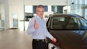 Mature man shows thumb up near the car at the dealership stock footage