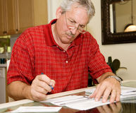 Mature Man Signing Papers. Handsome mature man signing papers beside a stack of bills Royalty Free Stock Photos