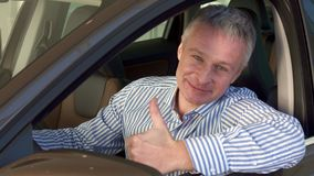 Mature man sits into the car at the dealership stock photo