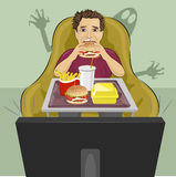 Mature man sits in chair eating hamburger and watching a horror movie on TV Stock Photos
