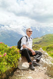Mature man sits on top of a mountain Royalty Free Stock Photos