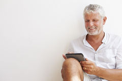 Mature Man Sitting Against Wall Using Digital Tablet Royalty Free Stock Images
