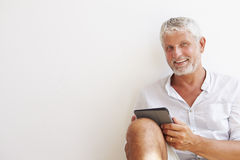 Mature Man Sitting Against Wall Using Digital Tablet Royalty Free Stock Photography