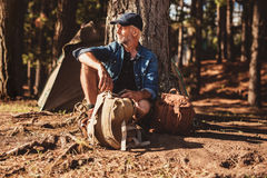 Mature man sitting alone at campsite with backpack Stock Image