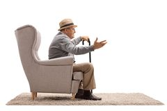 Mature man sitting in an armchair and talking Royalty Free Stock Photos