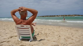 Mature man sitting on a beach chair and looking at the sea enjoying vacation stock video