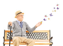 Mature man sitting on a bench and looking at butterflies Royalty Free Stock Photos