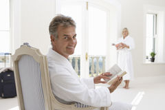Mature man sitting with book, smiling, portrait, woman standing in background Royalty Free Stock Photo