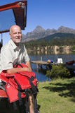 Mature man sitting in boot of parked SUV, holding red life jacket, smiling, portrait, lake and jetty in background Stock Photos