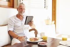 Mature Man Sitting At Breakfast Table Using Digital Tablet Royalty Free Stock Photos