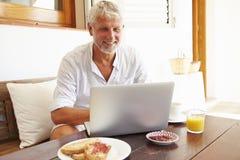 Mature Man Sitting At Breakfast Table Using Laptop Stock Photos
