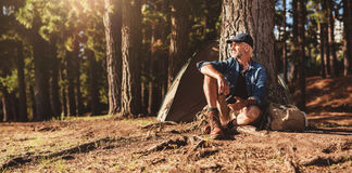Mature man sitting at a campsite. Portrait of senior man sitting by a tree with a tent in background. Mature man sitting at a campsite royalty free stock photography