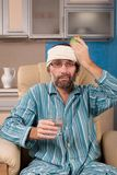 Mature man sitting in chair with glass of water Stock Photos