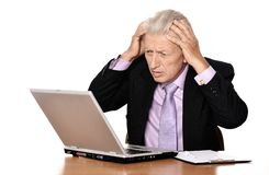 Mature man sitting at the computer. On a white stock photos