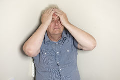 Mature man sitting in the corner of the room looking worried Stock Photos