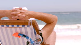 A mature man is sitting on a deck chair. On a beach stock footage