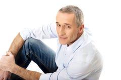 Mature man sitting on the floor Stock Photography