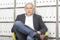 Mature man sitting in front of a shelf wall with documents folder Royalty Free Stock Image